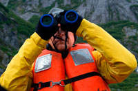 Juneau, Alaska, USA. Passenger with binoculars on cruise ship Safari Endeavour at anchor at Fords Terror, Endicott Arm, Tongass National Forest, Juneau, Alaska, USA. Cliff-walled fjords sliced into the mountainous mainland are on tap today as you slowly slip into an area widely acclaimed as the most beautiful in Alaska.