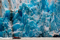 Juneau, Alaska, USA. Safari Endeavour cruise passengers in an inflatable boat in front of Dawes Glacier calves into the Endicott Arm fjord of Tracy Arm in Fords Terror Wilderness, Southeast, Alaska. Cliff-walled fjords sliced into the mountainous mainland are on tap today as you slowly slip into an area widely acclaimed as the most beautiful in Alaska. With more designated Wilderness Areas than any state in the nation, the finest include Endicott Arm and Ford's Terror, a pristine tidal inlet and fjord.