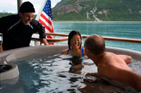 Juneau, Alaska, USA. Passengers enjoying hot tub on cruise ship Safari Endeavour anchgored Scenery Cove Thomas Bay Tongass National Forest Alaska USA.  Big trees, big birds, big fish, big bears, immense peaks wrapped in great glaciers that break off into bays where great whales spout: This is Southeast Alaska, the state's panhandle. It separates northern British Columbia from the open Pacific with a chain of misty, fjord-footed mountains and a jigsaw puzzle of more than a thousand islands.