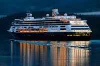 Juneau, Alaska, USA. Zaandam, sailing near the South Franklin dock, at night, Juneau, Alaska. Designed to carry fewer guests while providing more space for maximum comfort, ms Zaandam is a prize in the mid-size ship category. Offering spacious public areas and plush accommodations, many staterooms have private verandahs.