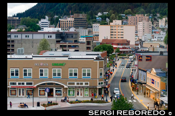 Juneau downtown, from the Mount Roberts Tramway. Alaska. USA. Diferents shops and stores in Juneau. South Franklin Street. The City and Borough of Juneau is the capital city of Alaska. It is a unified municipality located on the Gastineau Channel in the Alaskan panhandle, and is the second largest city in the United States by area. Juneau has been the capital of Alaska since 1906, when the government of what was then the District of Alaska was moved from Sitka as dictated by the U.S. Congress in 1900. The municipality unified on July 1, 1970, when the city of Juneau merged with the city of Douglas and the surrounding Greater Juneau Borough to form the current home rule municipality. The area of Juneau is larger than that of Rhode Island and Delaware individually and is almost as large as the two states combined. Downtown Juneau  is nestled at the base of Mount Juneau and across the channel from Douglas Island. As of the 2010 census, the City and Borough had a population of 31,275. In July 2013, the population estimate from the United States Census Bureau was 32,660, making it the second most populous city in Alaska after Anchorage.(Fairbanks is however the second-largest metropolitan area in the state, with more than 97,000 residents.) Between the months of May and September, Juneau's daily population can increase by roughly 6,000 people from visiting cruise ships.