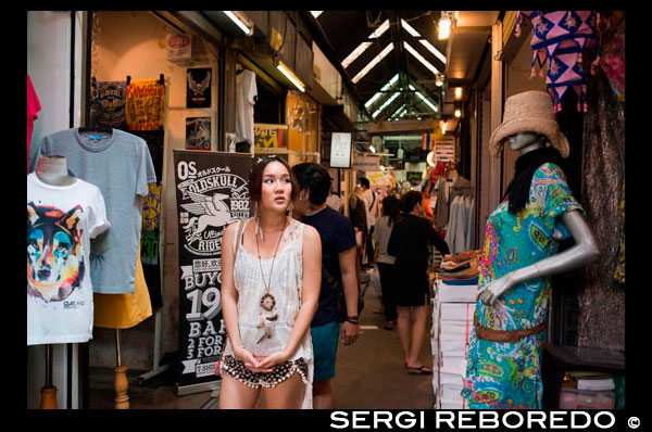 Woman buying clothes in stores at Chatuchak Weekend Market or Jatujak Market; is one of the world's largest weekend markets covers area of 70 rai (27 Acres) altogether divided into 27 Sections, contains more than 15,000 booths selling goods from every part of Thailand. Chatuchak Weekend Market,is very popular shopping centre to Thais and has become a popular place to tourists and foreigners who stay in Bangkok, has over 200,000 visitors each day(SAT-SUN) 30% is foreign. There are almost everything can be found here at a bargaining local price (not a tourist price), and most vendors actually come from local factories, like antique wood carving, clay handicrafts, local souvenirs from every parts of Thailand, Buddhist amulets, wooden funitures, hand made decorated flowers, plant, ceramic wares, dools, Thai Bejarong, Chinese wares, graden decorated plants, stones, trendy fashions, silk, hill-tribe outfits, fluffy dogs and more miscellaneous, etc.