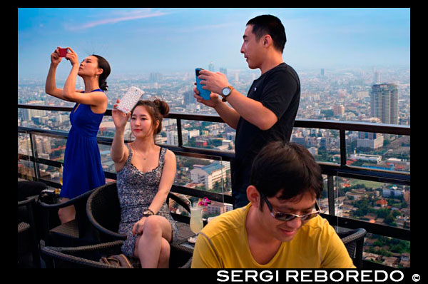 Asian people taking pictures. Banyan Tree Rooftop Vertigo & Moon Bar, Restaurant, , Bangkok , Thailand. View of the city, Vertigo Bar and Restaurant, roof of the Banyan Tree Hotel, at dusk Bangkok, Thailand, Asia. Reaching for the clouds at Vertigo and Moon Bar on the 61st floor of the Banyan Tree hotel is one of the best ways to end a long day in Bangkok. There is no lack of rooftop bars in town but Vertigo has always been amongst the favourites. With an unusual narrow and elongated shape, the entire top of the building is occupied by both the bar and the restaurant and gives the unusual impression of being aboard a spaceship in the sky. Located on Sathorn road, a very large busy avenue peppered with tall glass and metal skyscrapers and not far from the Lumpini park and Silom area, Banyan Tree is a name often associated with luxury. The hotel and its unusual design might be a bit aging, but once you step inside the lobby, you're still aware of this sophisticated yet relaxed atmosphere. From the lobby, a fast lift will take you to the 60th floor where you find the popular Bai Yun Chinese restaurant, walk pass it and up a flight of stairs that leads you outdoors. You better not be afraid of heights, as Bangkok will be laid out below you the moment you step outside. What surprises people the most is to walk out on a rooftop with absolutely nothing above you. Often similar venues would have a roof or a wall or even the continuing structure blocking part of the view. Not here… the designers have successfully eliminated anything that could block your vision and the impression is accentuated by the rather slim appearance of the building… it just appears narrow of course; there's still a 327 room hotel underneath! But the elongated shape hosting the Moon Bar on one end and the Vertigo restaurant is certainly impressive; this spaceship has an open-air bridge connecting the two areas hovering majestically above the city.