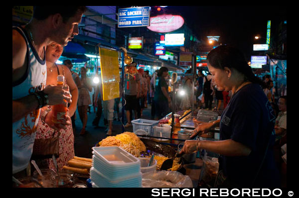 "khao san road, noodles street stall. Food stall. Bangkok. Khaosan Road or Khao San Road is a short street in central Bangkok, Thailand. It is in the Banglamphu area of (Phra Nakhon district) about 1 kilometre (0.62 mi) north of the Grand Palace and Wat Phra Kaew. ""Khaosan"" translates as ""milled rice"", a reminder that in former times the street was a major Bangkok rice market. In the last 20 years, however, Khaosan Road has developed into a world famous ""backpacker ghetto"". It offers cheap accommodation, ranging from ""mattress in a box"" style hotels to reasonably priced 3-star hotels. In an essay on the backpacker culture of Khaosan Road, Susan Orlean called it ""the place to disappear"".  It is also a base of travel: coaches leave daily for all major tourist destinations in Thailand, from Chiang Mai in the north to Ko Pha Ngan in the south, and there are many relatively inexpensive travel agents who can arrange visas and transportation to the neighbouring countries of Cambodia, Laos, Malaysia, and Vietnam. Khaosan shops sell handcrafts, paintings, clothes, local fruits, pirated CDs, DVDs, a wide range of fake IDs, used books, plus many useful backpacker items. During late evening, the streets turn into bars and music is played, food hawkers sell barbecued insects, exotic snacks for tourists, and there are also locals flogging ping pong shows. There are several pubs and bars where backpackers meet to discuss their travels. The area is internationally known as a center of dancing, partying, and just prior to the traditional Thai New Year (Songkran festival) of 13-15 April, water splashing that usually turns into a huge water fight. One Thai writer has described Khaosan as ""...a short road that has the longest dream in the world"".[2] A Buddhist temple under royal patronage, the centuries-old Wat Chana Songkram, is directly opposite Khaosan Road to the west, while the area to the northwest contains an Islamic community and several small mosques."