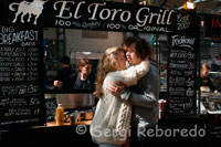 "A couple kissing in front of ""El Toro Grill"" Restaurant in St George's Market. The Markets area of Belfast used to have many different markets, including a pig market and a potato market. St Georges still has it's traditional fish, fruit and veg market every Friday (along with an assortment of other household items) and every Saturday there is a Farmer's Market. At the Farmer's Market you can buy locally grown produce, including ostrich and venison, and homebaked goods. There are also plants for sale.  In the run up to Christmas, there are several Craft Fairs. Each year these fairs get better and better and are an excellent outlet for buying local and Irish made products for gifts or special treats for yourself. There are people demonstrating their crafts such as ironmongers and woodworkers. There are also beautiful knits and hand sewn items. Admission is sometimes free and sometimes GBP2 which includes a cup of tea. There is even a kiddies table so the youngsters can be occupied. I am always impressed with the quality of the crafts that are on offer."