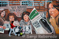 "We Demand POW Status Now. ""Forced to endure years of brutality, humiliatioon, degradation and torture, the prisoners embarked on hunger-strike, 27th October 1980"". Falls Road Belfast, Northern Ireland International Wall, Falls Road, Belfast The subjects change with the exception of Guernica. LIkewise ""Free Marian Price"" has been added to all the paintings with the exception of Guernica. As one of the so-called ""Price sisters"", Price was jailed for her part in the IRA London bombing campaign of 1973. She was part of a unit who placed four car bombs in London on 8 March 1973. The Old Bailey (Central Criminal Court and Hillgate House – a Government Building) and Whitehall army recruitment centre were damaged with 200 injured and one man died of a heart attack. The two sisters were apprehended along with Hugh Feeney and seven others as they were boarding a flight to Ireland. They were tried and convicted at the Great Hall in Winchester Castle on 14 November after a two days of deliberation by the jury. Marian Price was sentenced to two life terms. She and her sister Dolours Price, along with Gerry Kelly and Hugh Feeney, immediately went on hunger strike in a campaign to be repatriated to a prison in Northern Ireland. The hunger strike lasted over 200 days, with the hunger strikers being force-fed by prison authorities for 167 of them. In an interview with Suzanne Breen, Marian described being force-fed: Four male prison officers tie you into the chair so tightly with sheets you can't struggle. You clench your teeth to try to keep your mouth closed but they push a metal spring device around your jaw to prise it open. They force a wooden clamp with a hole in the middle into your mouth. Then, they insert a big rubber tube down that. They hold your head back. You can't move. They throw whatever they like into the food mixer – orange juice, soup, or cartons of cream if they want to beef up the calories. They take jugs of this gruel from the food mixer and pour it into a funnel attached to the tube. The force-feeding takes 15 minutes but it feels like forever. You're in control of nothing. You're terrified the food will go down the wrong way and you won't be able to let them know because you can't speak or move. You're frightened you'll choke to death."