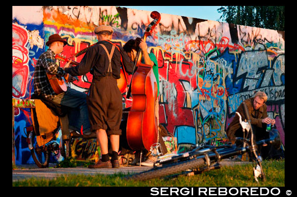 "Musicians. Buskers by the Wall in Mauerpark Berlin in evening light Germany. Mauerpark is a public linear park in Berlin's Prenzlauer Berg district. The name translates to ""Wall Park"", referring to its status as a former part of the Berlin Wall and its Death Strip. The park is located at the border of Prenzlauer Berg and Gesundbrunnen district of former West Berlin. In the 19th and 20th centuries, the Mauerpark area served as the location of the Old Nordbahnhof (""Northern Railway Station""), the southern terminus of the Prussian Northern Railway opened in 1877-78, which connected Berlin with the city of Stralsund and the Baltic Sea. Soon after it lost its role as a passenger station to the nearby Stettiner Bahnhof and remained in use as a freight yard. In 1950 the Stettiner Bahnhof took the name Nordbahnhof because of its role in Berlin's public transportation system, and the Old Nordbahnhof became known as Güterbahnhof Eberswalder Straße. It was finally closed after the building of the Berlin Wall in 1961. When viewed from above, one can still see remains of the railroad tracks running towards the former station from the Ringbahn."