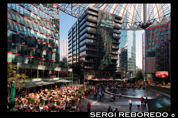 inside Sony Center at Potsdamer Platz in Berlin. Potsdamer Platz (German: [?p?tsdam? plats] ( listen), literally Potsdam Square) is an important public square and traffic intersection in the centre of Berlin, Germany, lying about 1 km (1,100 yd) south of the Brandenburg Gate and the Reichstag (German Parliament Building), and close to the southeast corner of the Tiergarten park. It is named after the city of Potsdam, some 25 km (16 mi) to the south west, and marks the point where the old road from Potsdam passed through the city wall of Berlin at the Potsdam Gate. After developing within the space of little over a century from an intersection of rural thoroughfares into the most bustling traffic intersection in Europe, it was totally laid waste during World War II and then left desolate during the Cold War era when the Berlin Wall bisected its former location. Since German reunification, Potsdamer Platz has been the site of major redevelopment projects. Potsdamer Platz began as a trading post where several country roads converged just outside Berlin's old customs wall. The history of Potsdamer Platz can probably be traced back to 29 October 1685, when the Tolerance Edict of Potsdam was signed, whereby Frederick William, Elector of Brandenburg-Prussia from 1640 to 1688, allowed large numbers of religious refugees, including Jews from Austria and Huguenots expelled from France, to settle on his territory. A key motivation behind the Edict was so the Elector could encourage the rapid repopulation, restabilising and economic recovery of his kingdom, following the ravages of the Thirty Years' War (1618–48). Altogether up to 15,000 Huguenots made new homes in the Brandenburg region, some 6,000 of these in its capital, Berlin (indeed, by 1700 and for a while afterwards as much as 20% of Berlin's population was French-speaking). Two other things resulted from this huge influx. Firstly, Berlin's medieval fortifications, recently rebuilt from 1658 to 1674 in the form of a Dutch-style star fort, on an enormous scale and at great expense (and similar to examples still in extant today in the Netherlands like Naarden and Bourtange), became virtually redundant overnight; and secon