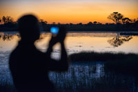 A man with binoculars enjoy the best sunsets in the Okavango Delta Fish Eagle Bar Camp Eagle Island Camp by Orient Express, outside the Moremi Game Reserve in Botswana. At Eagle Island will have one of the most unforgettable experiences: a safari boat. The nature as you have never imagined: hippos swimming in the water, crocodiles relaxed in the sun, herds of lions with their pups ... in short, a host of wildlife from the water. In the Delta will find more than a thousand species of animals including giraffes, leopards and elephants that will make your photos the envy of more than one. Finish the day with the sun, relaxing at the Fish Eagle Bar, one of the world's most romantic bars. Botswana is considered as one of the best kept secrets beauties and Africa. It is a natural wonder for his prodigious wildlife and variety of species thanks to its people and government are fully committed to safeguarding and protecting this natural treasure. That is why it has become a destination for safaris par excellence, where Big Five are the main stars of the show with some wonderful backdrop scenarios will not forget. A new opportunity to enjoy Botswana from the air to reach the semi-arid Savute in the Chobe National Park. At the heart of the park, considered the world capital of elephants, is the Savute, an area that personifies the eternal contrast of Africa. The Savute Elephant Camp is ideally located for its proximity to the river and found a few meters from a trough with stunning views that facilitate you enjoy wildlife without leaving the camp. The camp is located on the banks of the Savute Channel, offering a spectacular view of the elephants in their natural habitat.
