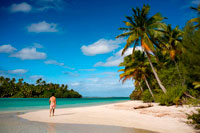 "Aitutaki. Cook Island. Polynesia. South Pacific Ocean. A tourist walks along the edge of the palm-fringed beach in One Foot Island.  Stamp Your Passport: Visit Aitutaki's One Foot Island, where you'll enjoy the incredible blue lagoon and a mouth watering beach barbecue, as well as a chance to receive Aitutaki's trademark One Foot passport stamp.. With a vast, sparkling lagoon rivaling Bora Bora's – but with a fraction of the visitors – Aitutaki just might be the world's most beautifully-remote island. Just a 45-minute flight from the main island of Rarotonga, Aitutaki and its surrounding atolls served as the tropical backdrop for ""Survivor: Cook Islands."" One of 22 islands in the Aitutaki atoll, One Foot Island (or Tapuaetai, ""one footprint"") is both dreamily-exotic and nearly deserted. It's the perfect place to laze on a powder-white beach or float in the knee-high lagoon. While it may look totally deserted, One Foot is home to one top attraction - a small hut containing one of the world's most remote post offices. Don't forget to bring your passport and you'll depart paradise with a footprint-shaped passport stamp to remember it by.  Atiu Island, also known as Enuamanu ('land of the birds') lies 187 kilometres north east of Rarotonga. The third-largest island in the Cooks is over eight million years old. It's also an ecologist's dream and a magnet for the adventurer. On the edge of the island's flat-topped central plateau you'll find Atiu Villas, the island's most developed vacation spot. You'll also find 28 untouched beaches that are almost unvisited – except by those seeking a beautiful, secluded spot. Beautiful Aitutaki. It's believed that the islanders on Aitutaki are descended from Ru, a seafaring warrior who settled there with his four wives."