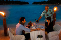Aitutaki. Cook Island. Polynesia. South Pacific Ocean. A couple enjoys a romantic dinner by the beach in Aitutaki Lagoon Resort & Spa Hotel. As the only resort directly on the world's most beautiful lagoon, The Aitutaki Lagoon Resort & Spa is truly blessed. This exclusive all-bungalow resort is one-of-a-kind in many other respects also. It is the only private island resort in the Cook Islands. The Aitutaki Lagoon Resort & Spa is a luxury resort destination on one of the most famous lagoons in the world. This Cook Islands paradise provides a naturally romantic setting, and the resort is a popular accommodation option, especially with honeymoon couples, those wishing to get married in Aitutaki, and anyone looking for an idyllic paradise island getaway. Guests may choose between beachfront and garden bungalows or opt for an overwater bungalow - the only destination in Cook Islands to offer overwater accommodation. The resort offers top hotel amenities, fine cuisine and a range of recreational activities: 7 Overwater bungalows - Cook Islands only overwater accommodation. 14 Beachfront and 16 Garden bungalows. Air-conditioning, TV/DVD/CD, king or queen beds, mini-bar etc. Relax at The Flying Boat Beach Bar & Grill. The Bounty Restaurant offers fine dining experience. Theme nights and Aitutaki entertainment. Complimentary activities include snorkeling, kayaking, biking, beach volleyball, guided hikes and cultural activities. Pay-for activities include deep sea fishing and scuba diving. Romantic wedding packages. Spa Facility at the SpaPolynesia, with extensive health and beauty treatments available.