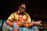 Aitutaki. Cook Island. Polynesia. South Pacific Ocean. Playing the ukulele (typical Polynesian guitar) in Aitutaki Punani Culture Tours. Tahitian ukulele. Ideally, the best way to learn the uke is to spend a bit of time in Tahiti, The Cook Islands, Rapa nui, Marquesas, Niue or Aotearoa(NZ) and just jam with the locals. Like all music in the pacific, the uke is generally learnt from a young age and gradually picked up over time from family or friends. Polynesian music is also learnt and played by ear, so when someone starts singing or playing a song you just listen for the key and join in. If you can play a Hawaiian uke then you should be able to pick up the Tahitian uke a lot faster as the chord patterns are basically the same. The main difference is the lead work and strumming techniques/patterns which take a bit of time to master. Koata from Kanua ukuleles has a series of excellent instructional videos (See below) to get you started.  Strumming: One of the hardest things about playing island ukes is the fast strum. On a guitar or Hawaiian uke, it's usually done flamenco style using all the fingers but with the Island style uke we just use a pick. The first thing you need to do is practice getting a rapid strum action by pivoting from the wrist. Once you get a clear and even vibrating sound going, you can then start creating funkier rhythms by flicking the wrist a bit harder on the particular down strum you want to stress.