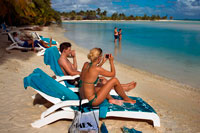Aitutaki. Cook Island. Polynesia. South Pacific Ocean. Some tourists take pictures and take a sun bath on the beach of Aitutaki Lagoon Resort & Spa Hotel.  Reinvigorate and rejuvenate body and soul. There are two spa options on Aitutaki to reinvigorate and rejuvenate body and soul. You deserve it!. Spa Polynesia at the Aitutaki Lagoon Resort & Spa has two separate spa facilities, and offer special treatments on the beach or by the pool as well as at the spa Here is a small selection from their menu: Maorooro Aromatherapy Massage, Tama Coconut Scrub, SpaPolynesia ThalassoAlgae Body Wrap, Vaevae SpaPedicure, Rekareka Pamper Pac, Navenave Indulgence Pack. They also offer honeymoon pamper packs. At the Pacific Resort Spa the range of treatments and therapies includes the unforgettable 4-hour Pure Indulgence treatment.