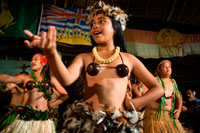 Atiu Island. Cook Island. Polynesia. South Pacific Ocean. Children dressed in traditional Polynesian dances and interpret Polynesian dances organized at Hotel Villas Atiu Atiu island. The Cook Islands lie northeast of New Zealand in the South Pacific Ocean. Cook Islanders are related to the Maori of New Zealand and the inhabitants of French Polynesia (commonly referred to as Tahiti). Cook Islands dance traditions are kept alive through festivals, celebrations and performances for tourists. Cook Islanders living abroad in the United States, Australia and New Zealand perform their dances as a form of cultural preservation.   Dances of the Cook Islands have much in common with other Polynesian dance forms. More widely known dance styles such as the hula from Hawaii and the tamure from Tahiti share similar mythology and dance themes. Cook Island dance performances often include chanting and singing among the dances, which tell stories or serve as spiritual communion with the Polynesian deities. Women's Choreography: Men and women dance together in performances, though in separate groups. The women's movements feature side-to-side movements of the hips. These movements are controlled by the knees. The hips must be energetic, with large, pronounced moves, but the upper body must stay graceful, with the shoulders remaining still. Some movement in the arms and hands may accompany the dance, but it must be carefully controlled. Men's Choreography:  While the women's silhouette is vertical with movements centered on the hips, men dance closer to the ground, with stronger movements in a distinctive bent-knee pose.