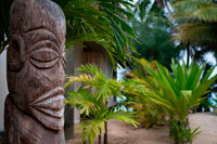 Rarotonga Island. Cook Island. Polynesia. South Pacific Ocean. Totem located outside the luxurious Little Polynesian Resort in Rarotonga. The Little Polynesian is surrounded with the kind of natural beauty that the South Pacific is renowned for. In 2005, the Little Polynesian underwent extensive renovations to unveil what can only be described as a literal re-creation to achieve once again a new level of service and amenities. Our magnificently built Ares (bungalows) have been designed with intricate attention to detail. Every unit uses traditional Cook Islands architecture combined with understated yet richly elegant décor. Little Polynesian a small luxury hideaway in Titikaveka on the island of Rarotonga overlooks a gorgeous white sand swimming beach with excellent snorkeling offshore and there are free kayaks to explore the turquoise lagoon. The no child policy ensures absolute privacy - making it the ideal place for honeymoons and romantic breaks. All rooms are non-smoking. The Little Polynesian offers all the amenities one would expect from the Cook Islands' most upscale boutique resort. The Luxury Beach Ares promise aimless days of looking out to the lagoon's turquoise waters and waking up to the gentle sound of waves, while the scent of tropical flowers fills the air around our garden villas. Traditional accents in the bungalows including Wild Hibiscus, Mangaian (coconut) sinnet weaving on beams as well as a thatched roof with natural Pandanus add to the ambience of our South Seas paradise. The scent of tropical flowers fills the air around the fourGarden Pia Tiare (Garden Villas) - providing a special experience that's close to nature. Like the Beach Ares, each is equipped with a spacious king size bed, out door shower and spa tub and bar fridge.