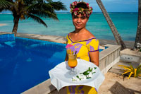 Rarotonga Island. Cook Island. Polynesia. South Pacific Ocean. A waitress serves delicious next to the poolside at the luxurious Little Polynesian Resort in Rarotonga. Nestled on the southern tip of Rarotonga, Little Polynesian Resort is a sophisticated playground for grown-ups. Here, serenity is certain, seclusion is guaranteed, and romance is everywhere. This is a Resort of unpretentious luxury where idyllic beaches beckon. The Beachfront Ares offer an uninterrupted vista of the azure lagoon while the view of tropical gardens from the garden thatched Ares is just as dazzling. Welcoming guests over the age of 15 years only, the primary clientele of the Resort are honeymooners and couples. Set on an unspoilt beach, the Resorts dwellings ooze Polynesian charm and luxury. Spend your days roaming the beaches and sipping fresh-fruit cocktails by the pool. Traditional architecture complements the island's natural beauty, and the bungalows are designed with every modern luxury, from gazebos with daybeds to outdoor showers. Experience the epitome of Polynesian luxury in our well-appointed beach and garden accommodations. The romance of traditional Polynesian architecture meets the creature comforts of the West in our modern interpretations of the local dwellings, or Are as they are known. Rendered in a minimalist palette of ivory and local woods, the spare elegance of our rooms takes the romance quotient up a notch. Traditional accents such as Wild Hibiscus, Mangaian (coconut) sinnet weaving on beams as well as a thatched roof with natural pandanus add to the ambience of our South Seas paradise.