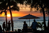 Rarotonga Island. Cook Island. Polynesia. South Pacific Ocean. Sunset on the beach in Hotel Crown Beach Resort & Spa.  Lit. Tourists taking photos. Parasols.  The Crown Beach Resort comprises of 22 villas nestled in four and a half acres of tropical garden, which leads onto a beautiful stretch of white sand beach. The stunning swimming pool has fantastic views of the beach and the serene flame tree and gardens; an ideal location for relaxing with a good book. After a hard days sunbathing or snorkelling you can make your way to the on-site spa for a therapeutic massage or treatment. Along with complimentary tropical breakfast and afternoon tea, this resort is home to two restaurants: The Windjammer, which serves delicious fish of the day and home made bread, and the beach side Cabana Bar and Grill, for more casual dining. Each comfortable villa is self contained ensuring maximum comfort, allowing you to enjoy natural warmth and charm of the Cook Islands in this attentive resort.