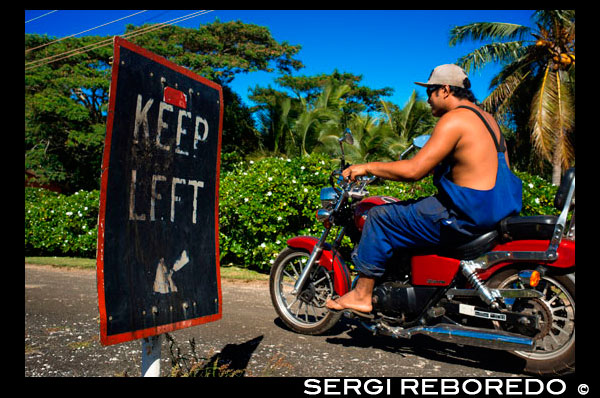 Atiu Island. Cook Island. Polynesia. South Pacific Ocean. An inhabitant of Atiu driving with his bike on the roads of the island next to a poster from Keep Left. Although Atiu is great for walking, a scooter (motorbike) or bicycle will allow you to explore more of the island at your own pace. Atiu Villas rents out scooters, bicycles and a jeep. Their own guests have priority but they will also rent to others. There are other businesses on the island renting out scooters though too and your accommodators can help organize this. You should let them know you might want to rent a scooter when booking your accommodation. Atiu Guesthouse and Atiu Homestay also have a four-wheel drive vehicle they rent out. Again it would pay to make enquiries and book ahead to ensure it is available. If you are doing some tours (very highly recommended) and some walking, you may only want to hire a scooter or jeep for one day - depending of course on how long you are staying on Atiu. Because of the small and personalized nature of tourism on Atiu, all of the accommodators will collect you from the airport and bring you to your accommodation. Transport may be on the back of a ute - travel like a local and enjoy the view! Fuel on Atiu is expensive and there is usually a cost for airport transfers although it may be included in your accommodation package. Check beforehand to avoid any misunderstandings when it's time to pay the bill. There is no public transport or taxi service on Atiu.