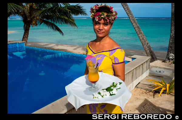 Rarotonga Island. Cook Island. Polynesia. South Pacific Ocean. A waitress serves delicious next to the poolside at the luxurious Little Polynesian Resort in Rarotonga. Nestled on the southern tip of Rarotonga, Little Polynesian Resort is a sophisticated playground for grown-ups. Here, serenity is certain, seclusion is guaranteed, and romance is everywhere. This is a Resort of unpretentious luxury where idyllic beaches beckon. The Beachfront Ares offer an uninterrupted vista of the azure lagoon while the view of tropical gardens from the garden thatched Ares is just as dazzling. Welcoming guests over the age of 15 years only, the primary clientele of the Resort are honeymooners and couples. Set on an unspoilt beach, the Resorts dwellings ooze Polynesian charm and luxury. Spend your days roaming the beaches and sipping fresh-fruit cocktails by the pool. Traditional architecture complements the island's natural beauty, and the bungalows are designed with every modern luxury, from gazebos with daybeds to outdoor showers. Experience the epitome of Polynesian luxury in our well-appointed beach and garden accommodations. The romance of traditional Polynesian architecture meets the creature comforts of the West in our modern interpretations of the local dwellings, or Are as they are known. Rendered in a minimalist palette of ivory and local woods, the spare elegance of our rooms takes the romance quotient up a notch. Traditional accents such as Wild Hibiscus, Mangaian (coconut) sinnet weaving on beams as well as a thatched roof with natural pandanus add to the ambience of our South Seas paradise. The Little Polynesian offers all the amenities one would expect from the Cook Islands' most upscale boutique resort. Our overbeach Ares (bungalows) promise aimless days of looking out to the lagoon's turquoise waters and waking up to the gentle sound of waves, while the scent of tropical flowers fills the air around our Pia Tiare (garden units). Whichever you choose, we guarantee you will be immersed in nature at the Little Polynesian.