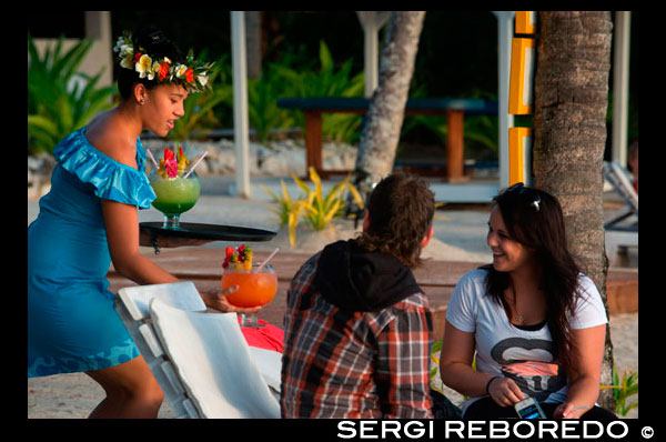 Rarotonga Island. Cook Island. Polynesia. South Pacific Ocean. A tourist couple enjoying huge cocktails by the beach in the Hotel Crown Beach Resort & Spa.  Crown Beach Resort & Spa presents a private secluded space for just 36 couples to escape in 5 acres of tropical gardens and an endless icing sugar beach that caresses a sparkling blue lagoon. Ridiculously romantic, Crown Beach Resort & Spa is located on the sheltered sunset coast of Rarotonga where 5 acres of botanical gardens and an endless icing sugar beach caresses a sparkling blue lagoon. Crown Beach Resort & Spa offers a private and secluded haven for just 42 couples to frolic in uninterrupted space and unhurried time. Our villas and suites present king bedrooms adorned with lavish textures in neutral tones that warm the soul - choose from your own private swimming pool or Jacuzzi. This place is sure to unleash your desire with the one you love. Crown Beach Resort & Spa is your key for pure bliss and luxurious romantic salvation.