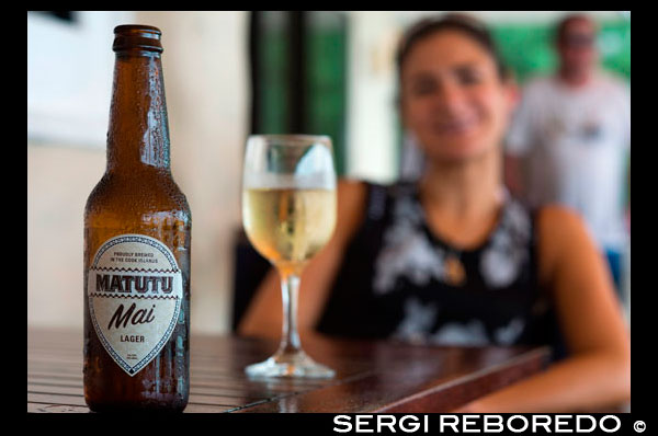 "Rarotonga Island. Cook Island. Polynesia. South Pacific Ocean. A girl sipping a Matutu Mai beer, typical beer of the Cook Island. Matutu Brewing Company is based in Vaka Takitumu on the island of Rarotonga. We are two families of patriotic Cook Islanders aiming to produce premium beers and beverages that will be iconic to the Cook Islands experience. Our beer is currently available in all reputable cafes, restaurants, resorts and bars in Rarotonga and in some outer islands resorts and cafes. Brewing is a long established practise in the Cook Islands called ""tumunu"".  Matutu is the only brewing company located in the Cook Islands. You can find us in the village of Tikioki, on the Island of Rarotonga. Matutu boutique beers are brewed in small batches using only premium brewing ingredients. We handcraft each brew, and bottle to order to ensure that our beer arrives fresh to you. At present we brew 'Mai' our Lager, 'Kiva' our Pale Ale and the recently launched 'Matutu' our draught. Mai – Lager Mai is an authentic Lager brewed with German Pilsner malt and the addition of four hops which give this beer its distinctive notes. Super Alpha and Hallertau hops are added early to this brew which ensures it's crisp, bitter taste, while the later additions of Saaz (B and D) give off the estery aromas and flavours. These combined with brewer's passion give you genuine flavours to savour while quenching your thirst."