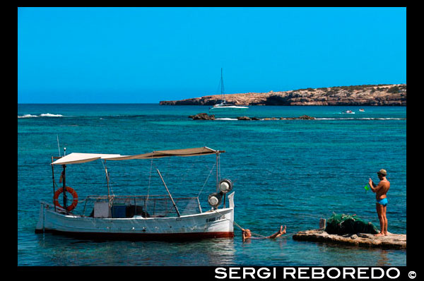 Els Pujols beach in Formentera. Tourists taken pictures with traditional fishing boat in summer day. Llaüt. Magnificent beach in the tourist area of Es Pujols, where you can find all the services: accommodation, shopping, restaurants, water sports.