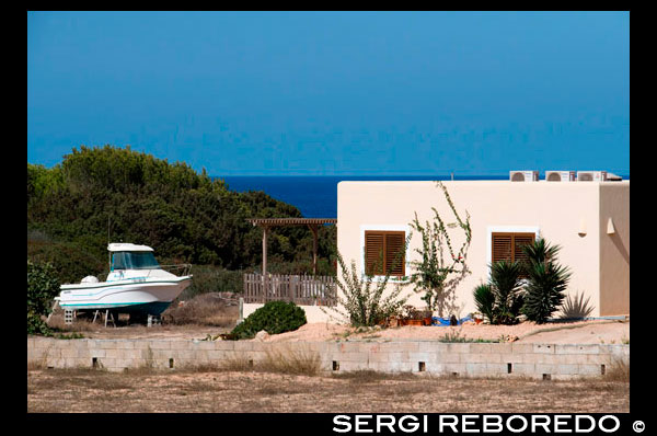 Typical white house of Formentera. Es Calo de San Agusti beach, Formentera Island, Mediterranean sea, Balearic Islands, Spain. Es Calo de San Agusti with boat in Formentera island  Spain; Formentera; island; typical; house; houses; boat; white; aged; ancient; architecture; art; balearic; bars; blue; building; buildings; coast; construction; country; door; environment; europe; fan; farm; formentera; holiday; home; house; ibiza; islands; landscape; masonry; mediterranean; nature; old; retro; rock; rural; rustic; spain; stone; street; style; texture; tile; tourism; town; traditional; travel; typical; view; village; wall; white; window; windows; wooden; yellow; balearic; Baleares; atrraction; destination; Europe; European; holiday; travel; islands; mediterranean; photos; place; spanish; sun; tourism; touristic; vacation; view; Balearics; beautiful; beauty; paradise; fun; happy; coastal; paradisiac; popular