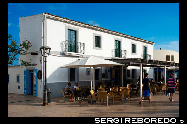 Tourists, Bars and restaurants in main square of Sant Francesc Xavier, San Francisco Javier, Formentera, Pityuses, Balearic Islands, Spain, Europe.   Spain; Formentera; island; balearic; Sant Francesc; Xavier; San Francisco; Francisco; Javier; main; square; central; typical; white; houses; house; bar; bars; rentaurant; restaurants; tourists; nice; town hall; day; daylight; daytime; during; europe; european; exterior; exteriors; formentera; holiday; holidays; island; islands; javier; journey; outdoor; photo; photos; pityuses; place; places; san; sant; shot; shots; small; south; southern; spain; spanish; square; squares; tourism; tourists; town; towns; travel; travelling; travels; trip; trips; vacation; vacations; village; villages; Baleares; atrraction; destination; Europe; European; holiday; travel; islands; mediterranean; photos; place; spanish; sun; tourism; touristic; vacation; view; Balearics; beautiful; beauty; paradise; fun; happy; coastal; paradisiac; popular
