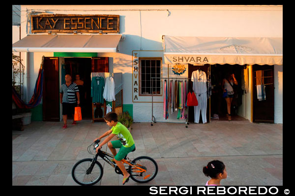 Tourists, Shops in main square of Sant Francesc Xavier, San Francisco Javier, Formentera, Pityuses, Balearic Islands, Spain, Europe.   Spain; Formentera; island; balearic; Sant Francesc; Xavier; San Francisco; Francisco; Javier; main; square; central; typical; white; houses; house; kid; bike; bicycle; shops; shop; kay; essence; fashion; store; tourists; nice; town hall; day; daylight; daytime; during; europe; european; exterior; exteriors; formentera; holiday; holidays; island; islands; javier; journey; outdoor; photo; photos; pityuses; place; places; san; sant; shot; shots; small; south; southern; spain; spanish; square; squares; tourism; tourists; town; towns; travel; travelling; travels; trip; trips; vacation; vacations; village; villages; Baleares; atrraction; destination; Europe; European; holiday; travel; islands; mediterranean; photos; place; spanish; sun; tourism; touristic; vacation; view; Balearics; beautiful; beauty; paradise; fun; happy; coastal; paradisiac; popular