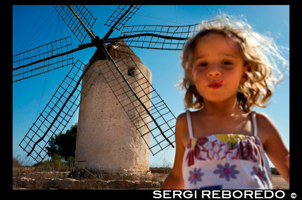 Funy girl in the windmill, Formentera, Balearic Islands, Spain. Old Windmill in el Pilar de la Mola on the island Formentera, Balearic Islands, Spain  Spain; Formentera; island; old; windmill; Pilar de la Mola; Mola; spanish; balearic; Baleares; atrraction; destination; Europe; European; holiday; travel; islands; mediterranean; photos; place; spanish; acient; architecture; countryside; destinations; nice; girl; child; travel; with; children; active; run; running; ecology; electricity; blonde; smile; energy; europe; european; exteriors; fields; formentera; historic; historical; horizontal; mill; mola; nobody; old windmill; outdoors; outside; power; production; renewable; rotates; rotating; rural; sightseeing; spain; spanish; sunshine; the balearic islands; tourism; tourists; traditional; travel; trees; trips; typical; wind; windmills; sun; tourism; touristic; vacation; view; Balearics; beautiful; beauty; paradise; fun; happy; coastal; paradisiac; popular