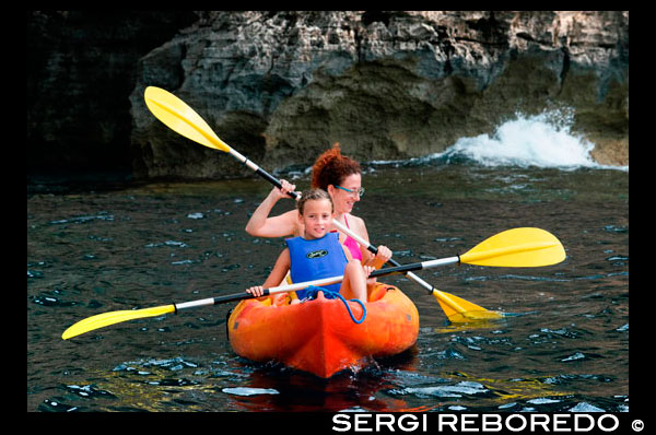 Mother and daughter doing kayaking on Cala Sahona, Formentera, Balearics Islands, Spain. Barbaria Cape. Spain; Formentera; kayak; kayaking; tradictional; beach; sea; Cala Sahona; Sahona; inlet; beautiful; mother; travel; with; child; children; kid; kids; woman; smile; people; girl; blue; clear; coast; coastline; crystalline; active; tourism; funny; happy; els; fishing; formentera; holiday; ibiza; idyllic; island; islands; landmark; landscape; mediterranean; nature; ocean; outdoor; paradise; pier; places; port; pujols; rail; railway; rock; scenic; sea; seascape; spain; stranded; summer; sunny; touristic; traditional; transparent; travel; turquoise; typical; vacation; water; white; wooden; island; balearic; Baleares; atrraction; destination; Europe; European; holiday; travel; islands; mediterranean; photos; place; spanish; sun; tourism; touristic; vacation; view; Balearics; beautiful; beauty; paradise; fun; happy; coastal; paradisiac; popular