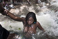 A woman bathing in one of the pools of Saut d'Eau to connect with Iwa. There are numerous diversifications (nanchons in Creole) from Iwas, which is invoked in a different order according to the ritual. The Iwa cited most frequently are those of the Rada rite, also known as sweet and good spirits. Almost all of the ceremonies consist of invocations to the Rada. At other times very specific to invoking the Petro rite, the Iwa hot, bitter or angry that you use to practice black magic. The Gede Iwa are associated with death and the passage to another world. There are also African Iwa as Ibo, Senegal and Kongo.