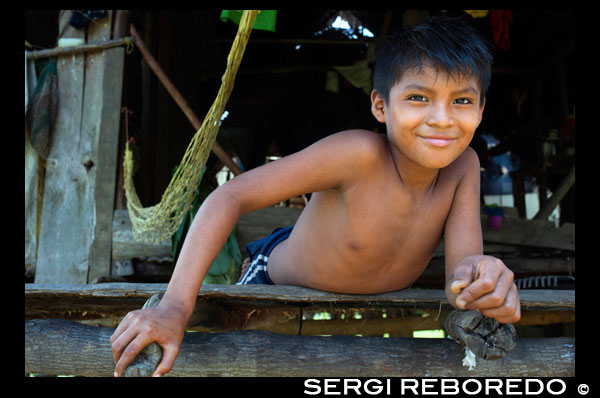 Boy in a House In The Ngobe Bugle Indian Village Of Salt Creek Near Bocas Del Toro Panama. Salt Creek (in Spanish: Quebrada Sal) is a Ngöbe Buglé village located on the southeastern end of Bastimentos island, in the Bocas del Toro Archipelago, Province and District of Panama.  The community consists of about 60 houses, an elementary school, handcrafts and general stores. The villagers depend mostly on their canoes for fishing and transportation although the village is slowly developing together with the whole archipelago.  Between the Caribbean Sea, with its mangroves, coral reefs, and paradisiacal islands, and the dense humid tropical forest of Bastimentos Island, lies the Ngobe community known as Salt Creek (Quebrada Sal).  Here, the local organization ALIATUR (Salt Creek Tourism Alliance) has created a project so that visitors to the Bocas del Toro Archipelago can get to know the culture of this indigenous community, its artisan crafts, its dances, and its stories.  Actions taken to promote environmental or social sustainability Four hiking trails in the surrounding forests allow the tourist to appreciate the rich fauna and flora of the region. Lodging and typical local food are offered for whoever wishes to visit for one or more days in the community.  In case this isn´t enough, the community´s proximity to the Bastimentos National Marine Park allows tourists to pay a quick visit to the marvelous Zapatilla Cays and to enjoy its beaches, coral reefs, and trail.