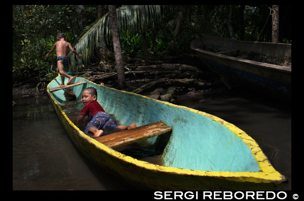 Kids play in one of the local boats used by the Ngobe Indians as their main form of transport, sheltered under a makeshift lean-to. Channel to entrance at The Ngobe Bugle Indian Village Of Salt Creek Near Bocas Del Toro Panama. Salt Creek (in Spanish: Quebrada Sal) is a Ngöbe Buglé village located on the southeastern end of Bastimentos island, in the Bocas del Toro Archipelago, Province and District of Panama.  The community consists of about 60 houses, an elementary school, handcrafts and general stores. The villagers depend mostly on their canoes for fishing and transportation although the village is slowly developing together with the whole archipelago.  Between the Caribbean Sea, with its mangroves, coral reefs, and paradisiacal islands, and the dense humid tropical forest of Bastimentos Island, lies the Ngobe community known as Salt Creek (Quebrada Sal).  Here, the local organization ALIATUR (Salt Creek Tourism Alliance) has created a project so that visitors to the Bocas del Toro Archipelago can get to know the culture of this indigenous community, its artisan crafts, its dances, and its stories.  Actions taken to promote environmental or social sustainability Four hiking trails in the surrounding forests allow the tourist to appreciate the rich fauna and flora of the region. Lodging and typical local food are offered for whoever wishes to visit for one or more days in the community.  In case this isn´t enough, the community´s proximity to the Bastimentos National Marine Park allows tourists to pay a quick visit to the marvelous Zapatilla Cays and to enjoy its beaches, coral reefs, and trail.