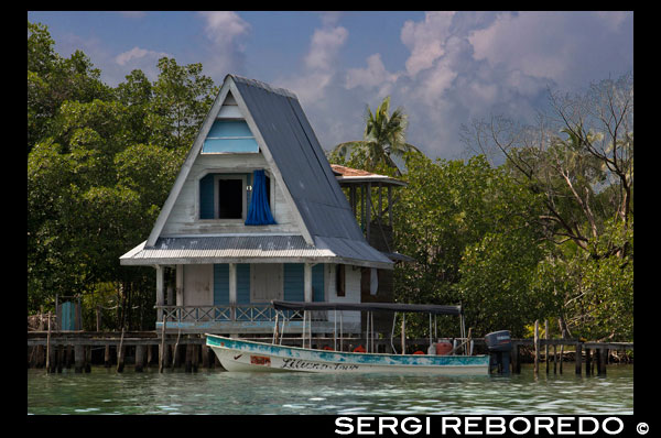 House on stilts over water with solar panels and dense tropical vegetation in background, Bocas del Toro, Caribbean sea, Panama. Tropical cabin over the Caribbean sea in the archipelago of Bocas del Toro, Panama. This is the ideal moment to visit these islands, to time travel and get lost in one of the hundreds of wonderful places that you can enjoy. It is a unique place to find yourself; its lush tropical vegetation, fauna only found in this part of the world, opportunities for diving and snorkeling the unbeatable Caribbean ocean, the possibilities and opportunities for an amazing experience are unbound. With an indescribable and overwhelming natural beauty, added to the great combination of races and ethnicities, living in harmony with indigenous, Western Caribe peoples, Latino's and extraneros, Bocas del Toro is not just a beautiful archipelago lost in time, blessed by nature -- Bocas del Toro is an example of coexistence and multi-cultural respect for everyone. Welcome to Bocas del Toro archipelago …..you will be amused and amazed, tempted beyond belief and for certain you will to take with you priceless memories of a different world. Enjoy your life….. Enjoy Bocas del Toro! Welcome to an unforgettable vacation.