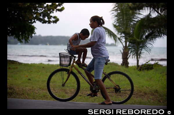 "Mother with his kid in a bicycle. Bocas del Toro, Panama. Bocas del Toro (meaning ""Mouth of the Bull"") is a province of Panama. Its area is 4,643.9 square kilometers, comprising the mainland and nine main islands. The province consists of the Bocas del Toro Archipelago, Bahía Almirante (Almirante Bay), Laguna de Chiriquí (Chiriquí Lagoon), and adjacent mainland. The capital is the city of Bocas del Toro (or Bocas Town) on Isla Colón (Colón Island). Other major cities or towns include Almirante and Changuinola. The province has a population of 125,461 as of 2010.  Christopher Columbus and his crew first visited the area in 1502. Bocas del Toro borders the Caribbean Sea to the north, Limón Province of Costa Rica to the west, Chiriquí Province to the south, and Ngöbe-Buglé Comarca to the east. The Río Sixaola forms part of the border with Costa Rica. An old railroad bridge spans the river between Guabito and Sixaola, Costa Rica. The bridge is a border crossing used by tourists going between destinations in Bocas del Toro and Costa Rica.  The province contains two national parks, Isla Bastimentos National Marine Park and La Amistad International Park. The Smithsonian Tropical Research Institute operates a research station on Colón Island just northwest of Bocas Town. There are many banana plantations in Bocas del Toro, often called the oro verde, or green gold of Central America."
