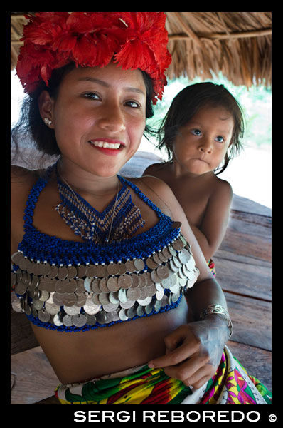 Portrait of native woman and child embera in the village of the Native Indian Embera Tribe, Embera Village, Panama. Panama Embera people Indian Village Indigenous Indio indios natives Native americans locals local Parque National Chagres. Embera Drua. Embera Drua is located on the Upper Chagres River. A dam built on the river in 1924 produced Lake Alajuela, the main water supply to the Panama Canal. The village is four miles upriver from the lake, and encircled by a 129.000 hectare National Park of primary tropical rainforest. Lake Alajuela can be accessed by bus and mini-van from the city of Panama. It lies an hour from the city, close to the town of Las Cumbres. From a spot called Puerto El Corotu (less a port than a muddy bank with a little store that serves as a dock to embark and disembark from canoes) on the shore of the lake, it takes 45 minutes to an hour to climb up the Rio Chagres to Embera Drua ina a motorized dugout. The village was founded in 1975 by Emilio Caisamo and his sons. They first called it community 2.60 as it was the name of the meteorological station constructed by the Panama Canal Commission located a little up river from the present community. The sons married and brought their wives to live in the community which later attracted more families. Most of the villagers moved out from the Darien Region--increasingly dangerous due to incursions by Colombian guerillas and drug traffickers--and to be closer to the city to have better access to its medical services and educational opportunities. In 1996, villagers adopted a name that reflects their identity and began to call their community Embera Drua. In 1998, the village totaled a population of 80. The social and political leadership of the village is divided between the Noko or village chief, the second chief, the secretary, the accountant and all the committees. Each committee has its president, and accountant, and sometimes a secretary. Embera Drua has a tourism committee that organizes itineraries and activities for groups of visitors and an artisans committee to assist artists in selling their intricate baskets and carvings. Such organization is a relatively new phenomenon but it is inspiring to see how the community has embraced it. The village of Embera Drua has its own NGO. Its goals are to support the village and promote tourism and its artisans. Thanks to their efforts, villagers of Embera Drua now own titles to their land. Their main goals are to assist the village in becoming economically self-sufficient. People from the village of Parara Puru lower down Chagres, have joined the NGO as well. If you would like to support their NGO, contact them directly.The climate is tropical with two distinct seasons. The rainy season lasts about seven months from April to October and the dry season is from November to March. The temperature is fairly constant during the year and varies from the high 80's (high 20's C) during mid-day to the 70's (low 20's C) at night. The landscape protects the village from the strong winter winds yet keeps it breezy enough that the village is almost free of biting insects.