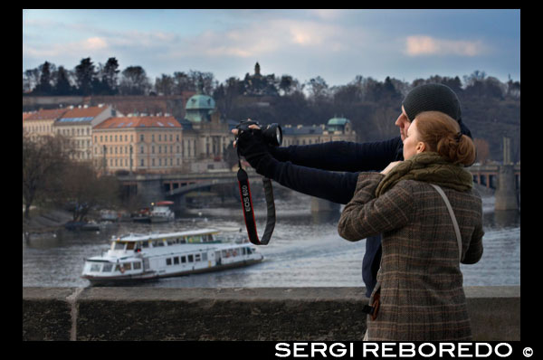 "Romantic Prague. A couple photo on the Charles Bridge. The Charles Bridge (Czech Karl? V most) is the oldest bridge in Prague, Vltava river and through the Old Town to the Lesser Town. It is the second oldest existing bridge in the Czech Republic. The need for a new bridge emerged after the old Judith Bridge was destroyed by a flood in 1342. This Romanesque bridge was named after the wife of King Ladislaus I. Astrologers and numerologists determined that Carlos IV should attend the settlement of the foundation stone at 5:31 AM on July 9, 1357. This moment can be stated as 135797531, and forms a palindromic sequence of ascending and descending odd digits, which is engraved on the tower of the Old City. The construction was supervised by Peter Parler, and led by a ""magister pontis"", Jan Ottl. The bridge was built with sandstone Bohemia. There is a legend that eggs were used to enrich the mortar used at the time of laying the blocks in order to make it harder. Although this can not be verified directly, recent analyzes have confirmed the existence of organic and inorganic ingredients in the mortero.1 The Charles Bridge construction lasted until the early fifteenth century. To financially support the work tolls charged task that initially belonged to the religious order of the Knights of the Cross with Red Star, and then the Old Town municipality (until 1815)"