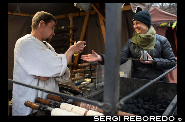 A woman buys delicious trdelník at a street stall. One of the sweets are trdelník Prague. Some cupcakes rolled and hollow, plated sugar, flour, nuts and cinnamon. In this position made ??them great. Trdelník (also known as Skalicky trdelník) is a cake tradicioal of Slovak cuisine (on the border of Slovakia and Moravia) .1 This is a rolled dough on a wooden skewer (whose name is Trdlo) and handle (Rotisserie) a charcoal fire while rotating mass on itself. The final form is that of a fire massecuite cylindrical and hollow inside, slightly smoky flavor with cinnamon and aromatzado. It is very traditional in street markets (in Prague), and is usually served as street food. Markéta Lehecková.