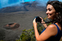 A female tourist photographing one of the boilers of the Piton de la Fournaise volcano. Also known as the 'volcano that smells like vanilla' is located on the French island of Reunion and typically erupts approximately every two years. After several days showing a critical activity, the October 14, 2010 the last eruption occurred violent volcano spit lava and gases expelled into the atmosphere, but fortunately did not end the life of any human. From what is clear is that the island of Reunion, the Indian Ocean's largest-has been shaped over thousands of years by the five volcanoes that watch from above and that this Piton de la Fournaise is the only one still active.