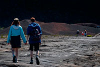 A couple making a trek over the lava of volcano Piton de la Fournaise. Reunion Island is formed by two volcanoes stratum mainly basaltic composition, juxtaposed on the ocean floor and partially emerged: the Piton des Neiges northwest, oldest and extinct 20,000 years ago, culminating at 3070 m. The Piton de la Fournaise is an active volcano that formed on the southeast side of the first and reaches 2631m altitude. The total volume emerged island km3 represents 0.8 x103 to be 1/32 of the total volume of the overall structure. Taking into account the hidden volume in the monoclinal fold of the plate, the part above represents only one hundredth of the total volume. The first eruptive events on the ocean floor at 4000 m depth are estimated occurred 4-5 my ago, the Piton des Neiges has now reached about 7000 m in height from the bottom of the ocean.