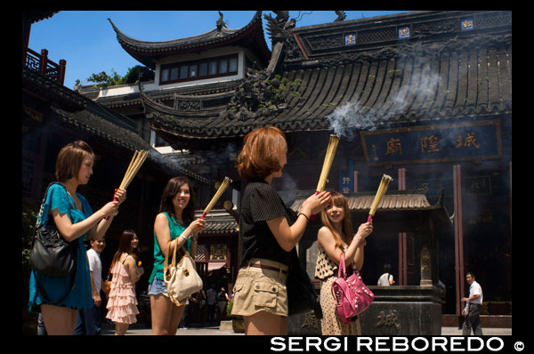 God Temple and pagoda, buddhist temple in Shanghai, burning joss sticks, incense. A women prays and laughs at Chenghuang Miao or City God Temple in Yu Yuan Gardens bazaar Shanghai, China. Located next to the Yuyuan Garden and also known today as the Yu Garden Market, the City God Temple (Chenghuang Temple) was built in the fifteenth century during the Ming Dynasty. Originally a temple built to honor the Han statesman Huo Guang (68 B.C.) The City God Temple is a Taoist temple which is composed of many halls such as the Grand Hall, Middle Hall, Bedroom Palace, Star Gods Hall, Yama Palace, Xuzhen God Hall. The temple had an area of more than 10,000 square meters including two gardens: West Garden (Yuyuan Garden) and East Garden. The City God Temple has a great influence on the residents of Shanghai. The religious festivals of the temple are considered to be the festivals for all Shanghai people.  Especially when the Sanxun festival (a day when the City God start to inspect his people) comes, nearly all people will come to the Temple to burn incense and worship the God, while all shops inside or close by would hang red lanterns to celebrate the festival. In addition, some folk arts, like cockfight, penmanship performance and acrobatics, are fairly attractive.