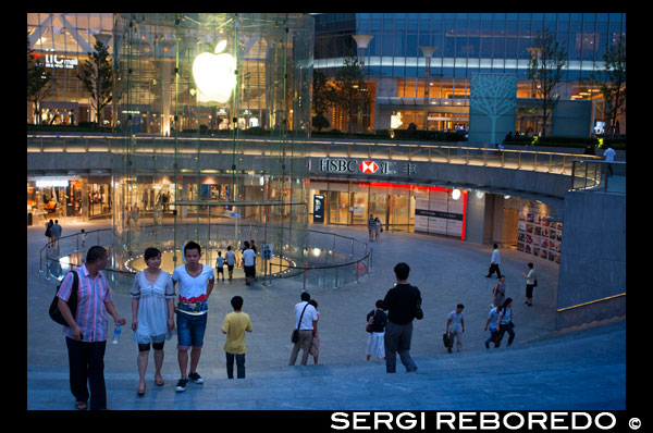 Apple computer store in Lujiazui financial district, in Pudong, in Shanghai, China. View of large modern Apple store in Shanghai China. Apple Store Pudong in front of Shanghai IFC South and North Tower (HSBC building) in Pudong District, Shanghai, China. Shanghai International Finance Centre, usually abbreviated as Shanghai IFC, is a commercial building complex and a shopping centre (branded Shanghai IFC mall) in Shanghai. It incorporates two tower blocks at 249.9 metres (south tower) and 259.9 metres (north tower) housing offices and a hotel, and an 85-metre tall multi-storey building behind and between the two towers.  Shanghai IFC is located in Lujiazui, in Pudong, Shanghai. It occupies a prominent position southeast of the Lujiazui roundabout, diagonally across from the Oriental Pearl Tower and across the road from Super Brand Mall. It is adjacent to Lujiazui Station on Metro Line 2, and can be accessed directly from the underground station via a tunnel.  The south tower of Shanghai IFC and part of the multistorey building was completed in 2009, while the north tower and the rest of the complex was completed in 2010. Work continued for several years afterwards on peripheral aspects of the development, including landscaping and footbridge connections to nearby buildings and Lujiazui Central Park.  The Ritz-Carlton Hotel occupies the south tower, while the north tower houses the current Shanghai headquarters of HSBC in China. Other prominent tenants of the complex include an Apple Store under the sunken forecourt of the building (topped by a cylindrical glass skylight rising from the forecourt), a multi-screen cinema, and a Citysuper supermarket. The remainder of the retail area is largely taken up by upscale chain restaurants and international luxury fashion brands.