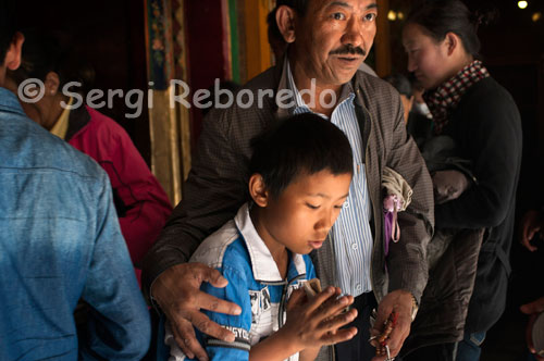 An old man with his son in Tsepak Lhakhang Monastery. Lhasa. Women make a procession around the temple to ask the god of longevity (Cherisi chepal) have a good birth, or elderly people to pray.