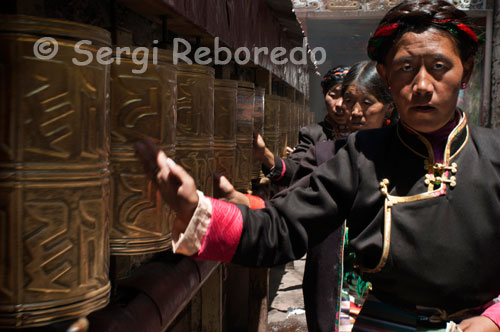 Several women spin the prayer wheels in Tsepak Lhakhang Monastery. Lhasa. Women make a procession around the temple to ask the god of longevity (Cherisi chepal) have a good birth, or elderly people to pray.