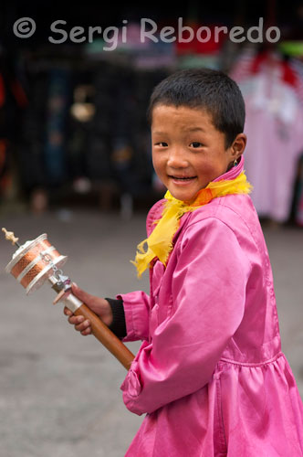 A Tibetan boy mill spins his prayer in the streets of Lhasa. Thousands of Tibetans debotos spin their prayer wheels, while doing the Kora around Kokhang and recite their prayers. Inside the mill there is a paper written with the prayer recited, so that when you spin once, as if reciting the prayer.