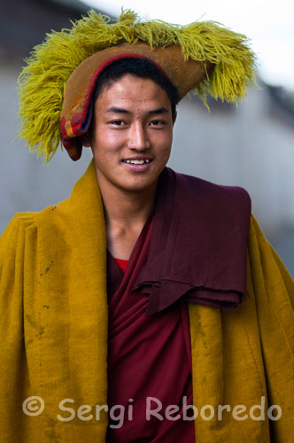 Portrait of a Buddhist monk dressed to go to prayer inside the Tashilumpo Monastery, located in Shigatse, Tibet. Tashilumpo monastery itself is a great city. Built in 1447 has traditionally been the home of the Panchen Lama. It contains many works of art and paintings, thankas, fresh and beautiful carvings.