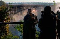 "A couple takes photos in Victoria Falls. Behind the bridge between Zambia and Zimbabwe.  The Victoria Falls Bridge crosses the Zambezi River just below the Victoria Falls and is built over the Second Gorge of the falls. As the river is the border between Zimbabwe and Zambia, the bridge links the two countries and has border posts on the approaches to both ends, at the towns of Victoria Falls, Zimbabwe and Livingstone, Zambia. The bridge was the brainchild of Cecil Rhodes, part of his grand and unfulfilled Cape to Cairo railway scheme, even though he never visited the falls and died before construction of the bridge began. Rhodes is recorded as instructing the engineers to ""build the bridge across the Zambezi where the trains, as they pass, will catch the spray of the Falls"". It was designed by George Anthony Hobson of consultants Sir Douglas Fox and Partners, not as is often stated, Sir Ralph Freeman, the same engineer who contributed to the design of the Sydney Harbour Bridge. At the time of the design of the Victoria Falls Bridge, Freeman was an assistant in the firm who, in those pre-computer days, was calculating stresses."
