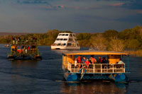 "Cruise along the Victoria Falls aboard the "" African Queen"".  Other boats sailing in the Zambezi River. Take a Sunset Cruise down the mighty Zambezi River. This Sundowner Cruise takes you down the Zambezi River for a beautiful journey!. The Zambezi Sunset River cruise is a superb way to relax and enjoy the beauty of the River. You may have the opportunity to see a variety of game; including hippo, crocodile, elephant and sometimes even rhino in their home environment, as well as enjoy the many different bird species."