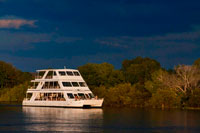 "Cruise along the Victoria Falls aboard the "" African Queen"".  Other boats sailing in the Zambezi River. This is the ""Lady Livingstone"" boat.  The newly built lady Livingstone famously known as ""The Jewel of the Zambezi"" has a capacity of 144 pax. Guests are met at their respective hotels/Lodges and transferred to the David Livingstone safari Lodge and Spa. The cruise takes place along the river boundary of the Mosi-Oa-Tunya National Park, total cruise time is approximately 2 hours. During the cruise, clients are likely to see hippos, crocodile and some good birdlife. Possible other game sightings are elephant, giraffe, buffalo and buck. An experienced guide accompanies each cruise and has good knowledge on the wildlife and local history of the area.  Excellent hot and cold snacks are served on board and the bar is well stocked with spirits, good wines, beers and soft drinks. Snacks and drinks are included in the price and served throughout the cruise.  Pick up times are 16h00 in summer (August to April) and 15h30 in winter (May to July)."